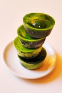 Grüne Eiswürfel aus Spinat auf Teller gestalpelt